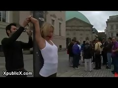 Blonde bound naked in a city square