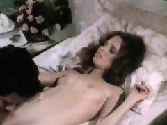 A guy and a girl are on a bed and he is taking her clothes off,...