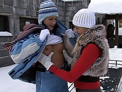 Two teenage girls are playing outdoors in the snow. They bare their...
