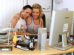 Two teenage girls are sitting at a desk, playing with the computer...