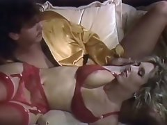 A guy and a blond girl are lying down on the couch. She is only...