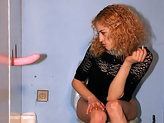A redheaded girl is having a pee on a toilet when a pink dildo...