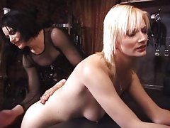 Submissive blond spanked by her two mistresses