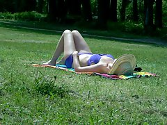 Attractive mom sunbathing in public park