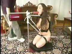 Woman in black lace stockings gets her pussy flogged and her mouth gagged with a big dildo