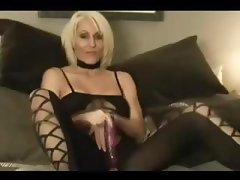 Mature blonde gal Jan B wears a sexy black outfit and toys her snatch