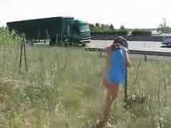 Mature exhibitionist shows her nude body near motorway