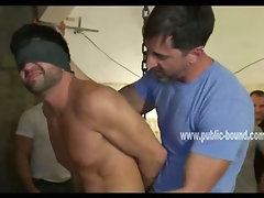 Tattooed and tied up gay man with big muscles is bent over and brutally fucked in his mouth