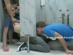 Beautiful teen boy gets to suck a lot of dicks in a public bathroom and is dominated