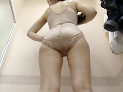 Lady who is trying on girdles and bodysuits in fitting room