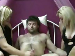 Two ladies take turns stroking his dick