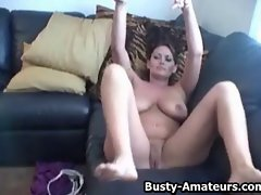 Chesty young woman Leslie masturbating on the couch