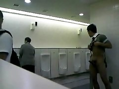 Man jacks of in public restroom for audience