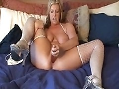 A white upholstered Big Bertha is beating her own meat with a dildo