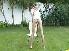 Skinny chick getting wet in the garden