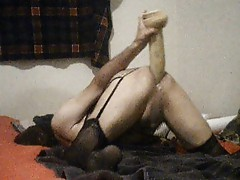 Crossdresser taking turns with three huge dildos