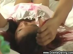 Dressed up asian doll with gloves gives handjob