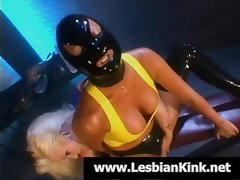 Slave in latex with a hood is getting fingered by her mistress