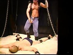 Muscular gay chained up getting stomped and his nuts squeezed