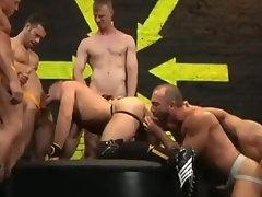 Gay pornstar sucks cocks at a gangbang