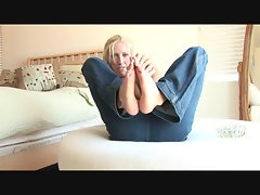 Slim girl in jeans teases her sexy feet
