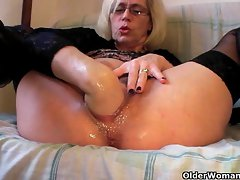 Whorish grandma in stockings fists her shaggy quim