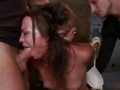 Bound brunette chokes on a hard throbbing boner