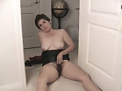 Furry milf sexpot looks into the camera while she rubs hairy pussy