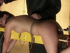 Man in black machine fucks brunette slave