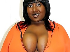 Big, beautiful, and busty black woman Ms. Squeez'em smiles for the camera inside an orange bra and panties set. She frees her big natural tits fr