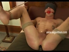 Hunk tied from bed naked with legs in the air and perverted by gay master getting a nice handjob