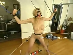Blonde hanged in ropes and with face bound in bondage mouth mask is tortured in bondage sex