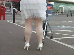 Babe in white seamed stockings is being filmed walking around