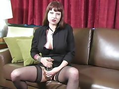 Busty brunette on a couch talking and toying with a water bottle