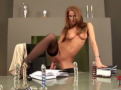 Redhead slut gets toyed up as she dips her slit with dildos on a desk