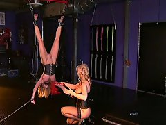 This poor  blonde whore, her body is tied up side down while an evil...