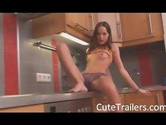 Thin girl teasing body on a kitchen unit