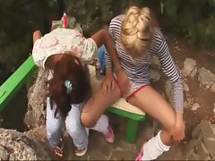 Two teen lesbians are outside and play with each other getting undressed