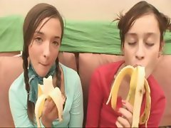 Two teens sit on the couch and eat bananas and then show titties