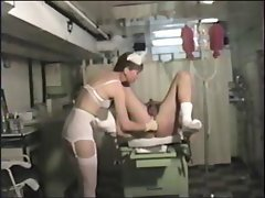 Brunette nurse has got the guy up on a table and massages his prostate