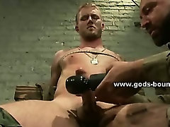 Strong chest of a gay is bound in thick rope while masters use clips to pervert him