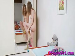Skinny brunette teen is changing clothes in front of a mirror