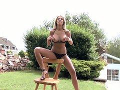 Clara G in black lingerie seducing on chair outdoor