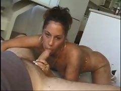 Between his legs sucking his cock