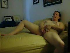 She rubs lotion into legs and masturbates