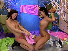 Two teenage girls are on the studio floor playing with some stuffed...