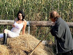 A guy is shifting hay and a teenage girl is watching him. They get...