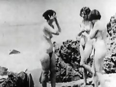 A man in a suit is on a free beach watching three naked women. He...