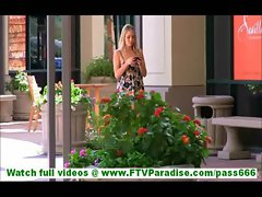Cassy blonde vamp walking outdoors with mobile phone
